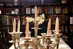 Shabbos candelabra with bookcase in the background