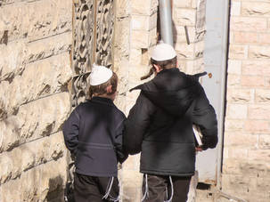 Two Yerushalmi boys holding hands and walking in Israel