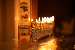 Silver oil menorah lit with bottle of oil behind