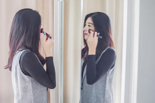 Woman putting on makeup in front of a mirror