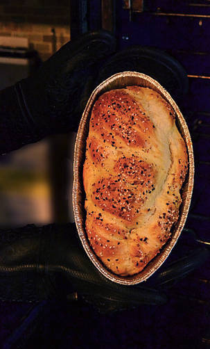 Gloved hands holding Challah in a pan