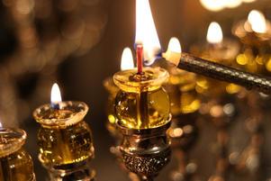 Candle lighting an oil menorah on Chanukah
