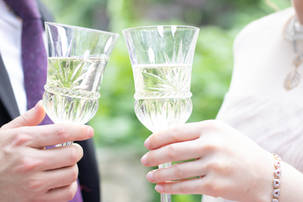 Engaged couple raising glasses in a toast to celebrate