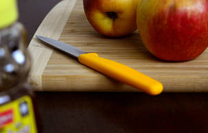 Close up of apples on a cutting board with knife, honey in the foreground