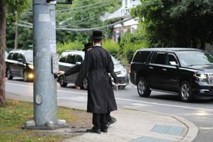 Two hasidic boys talking on a street corner