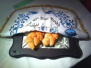 Challah on challah board with Shabbos challah cover
