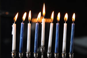 Blue and white lit candle menorah