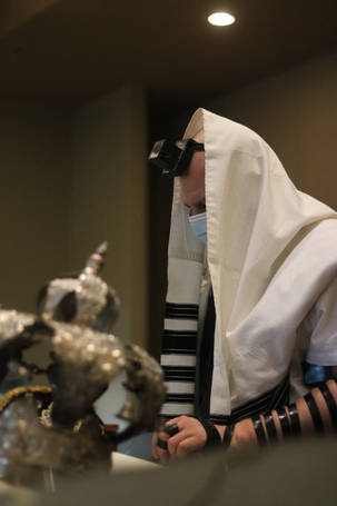 Man davening wearing talis, tefilin and mask, Sefer Torah crown in the foreground