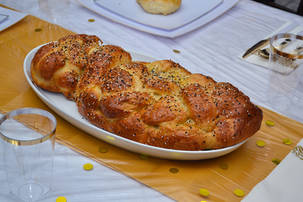 Large challah on a set table from above