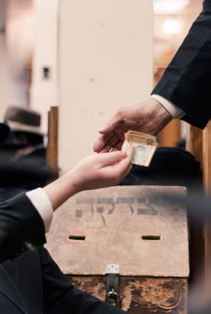 Handing over money to poor man in front of a tzedakah box