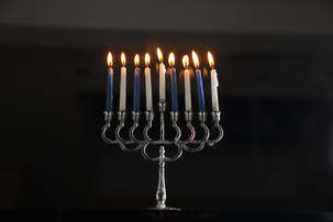 Silver menorah with white and blue candles lit on Chanukah