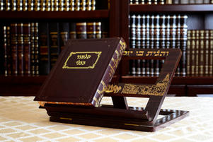 Closed gemara on a shtender with bookcase of sefarim in the background