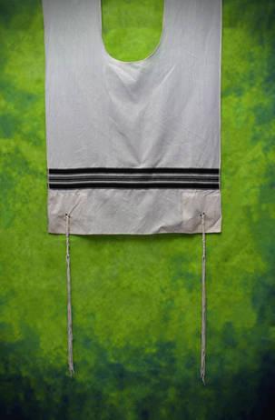 Tzitzis hanging on green background