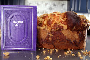 Loaf of challah with hafrashas challah booklet
