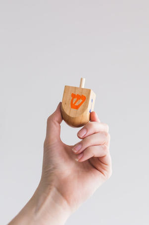 Hand holding wooden dreidel