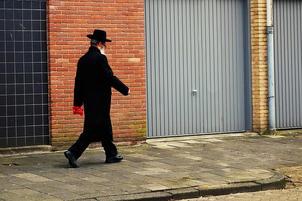 Jewish man in black hat and white beard walking