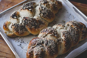 Challah on a tray with seeds and spices on top