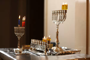 Three menorahs on a table lit on the second night of Chanukah