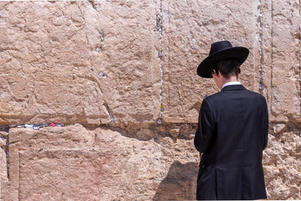 Man in black hat in front of the Kotel/Wailing Wall