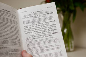 Hand holding a siddur open to Modeh Ani
