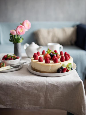 Classic New York Shavuos Cheesecake Sliced At Plate On Table with Flowers