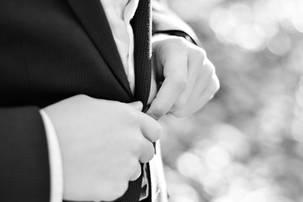 Bar mitzvah boy buttoning suit jacket