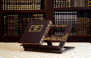 Closed gemara on a shtender with bookcase of sefarim in the background v2