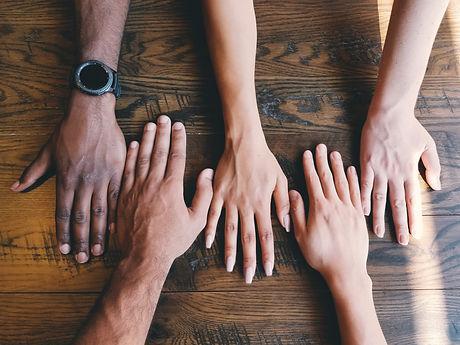 Viele Hände auf Holz