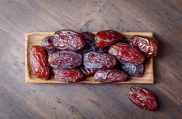 Juicy dates in a bowl on a old wooden ta