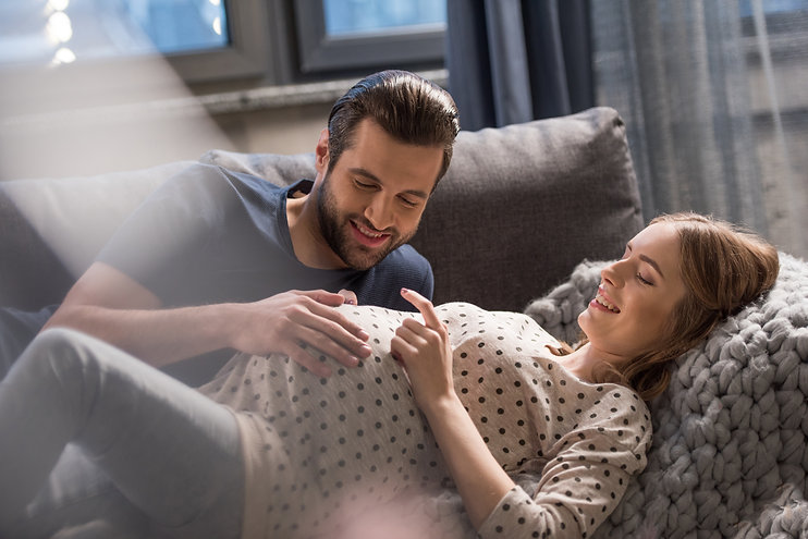 Happy man touching belly of smiling preg