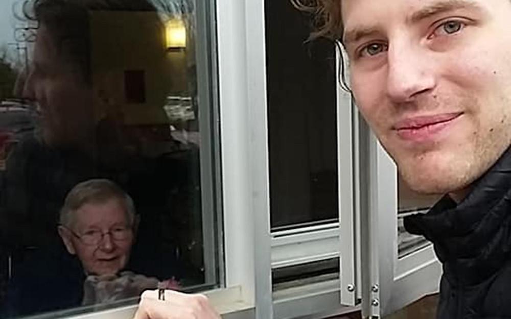 Zach DeBoer (캐나다 온타리오 Oakville에 있는 ClearView CRC 교인) 이 92세 생일을 맞은 그의 할머니 Alice DeBoer를 창문 넘어로 방문하고 있다.