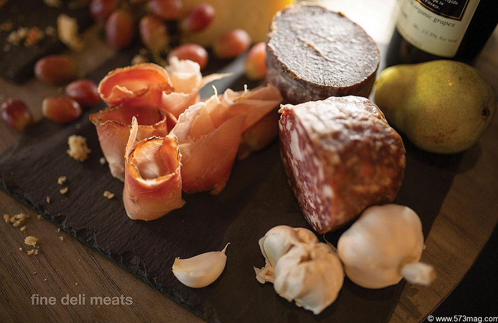 Rolled ham, chunks of sliced sausage, and garlic cloves on a wooden cutting board