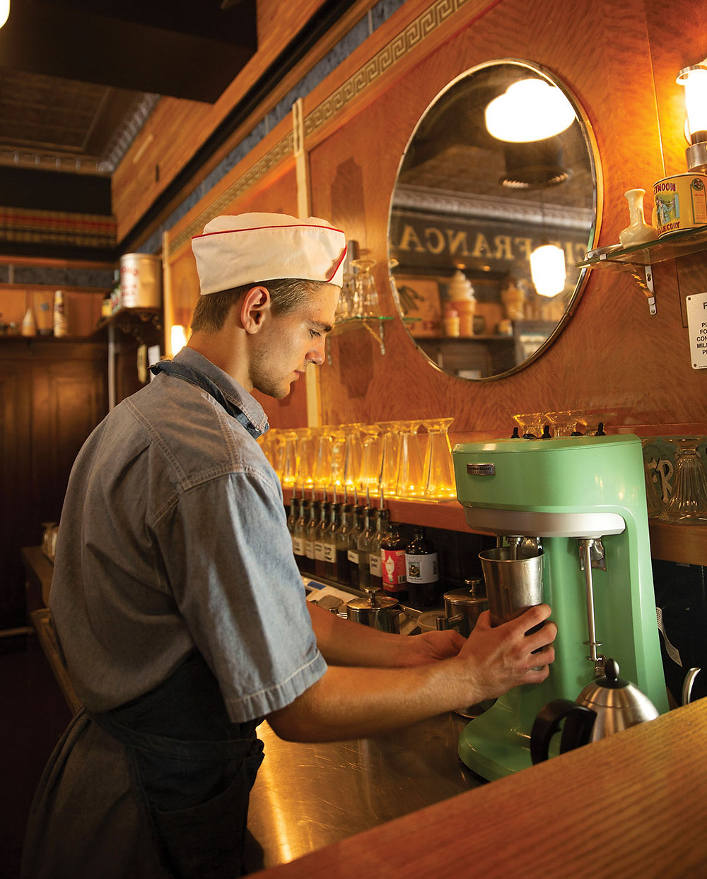 A young man in an old fashioned ice cream parlor hat and apron mixes a milk shake using a vintage mint condition and colored mixer front the 1940s