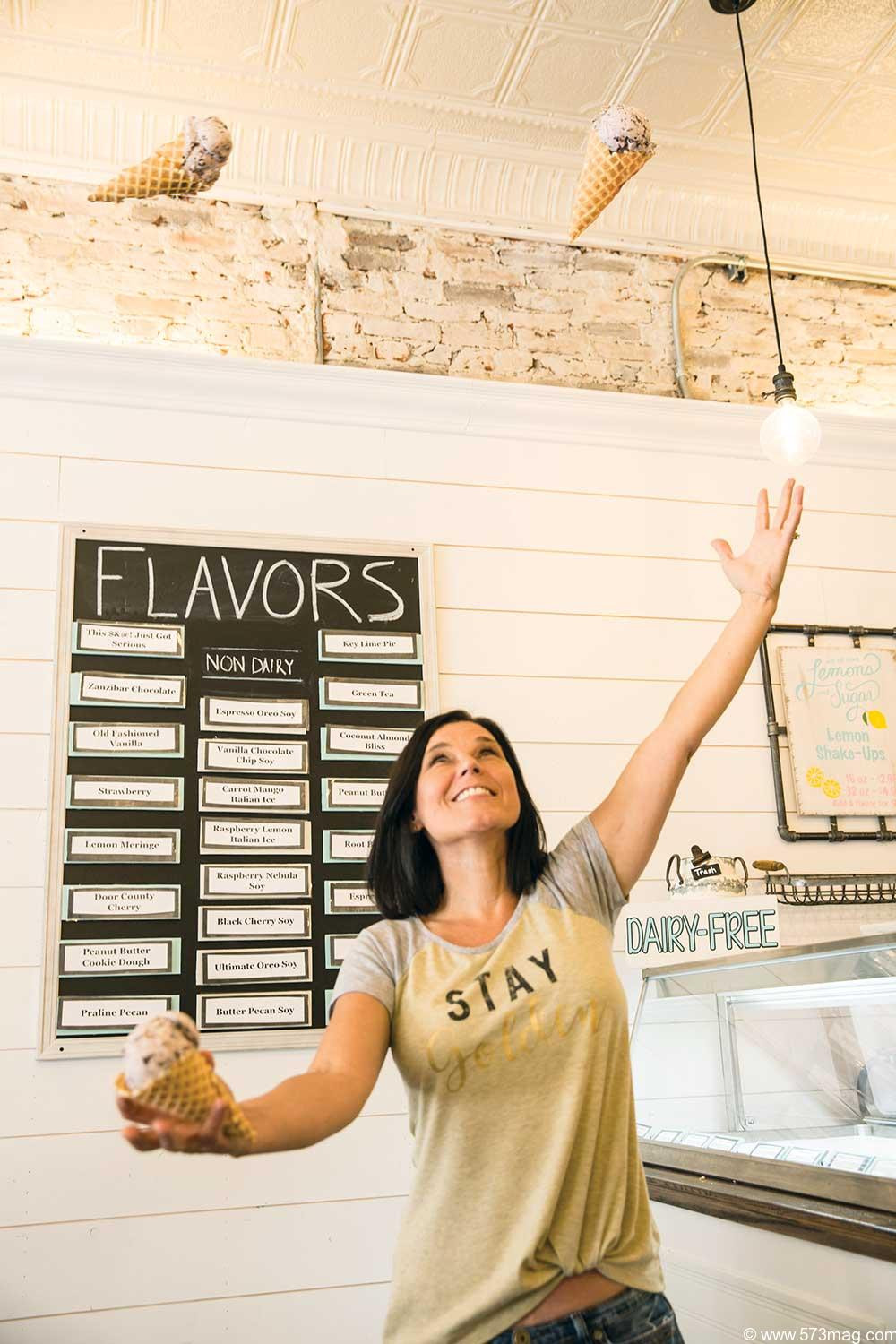 A beautiful woman juggles 3 ice cream cones tossing them high in the air