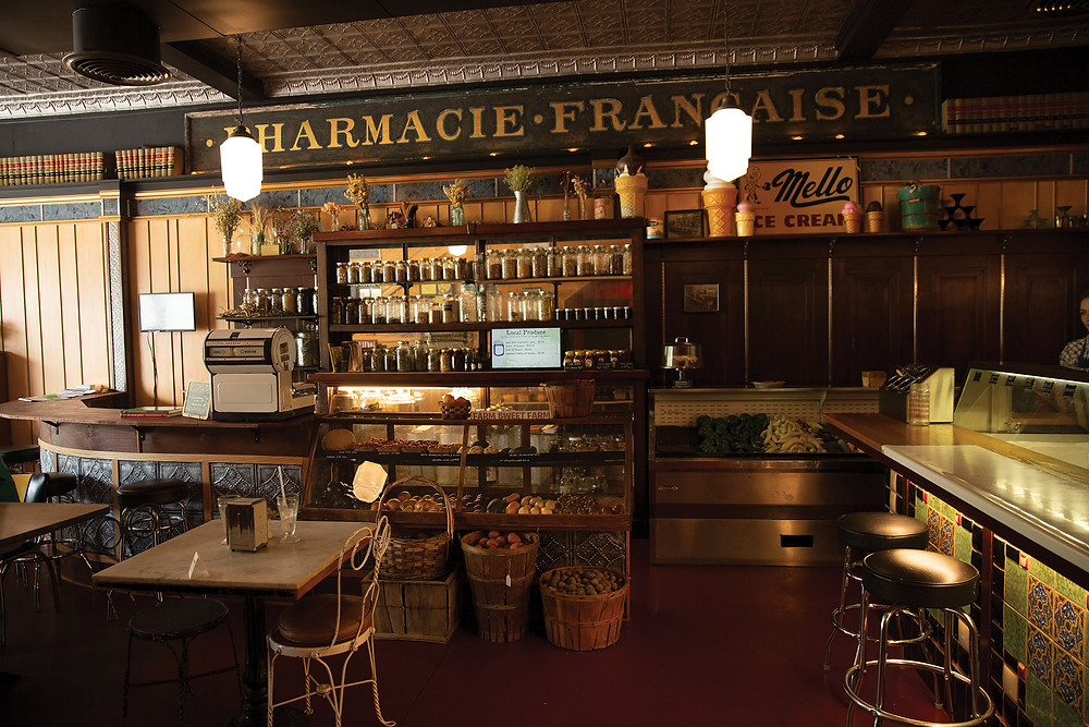 A store/dining area that looks like its from the 1940s with fresh produce in a display case and baskets, jars of dried herbs behind the counter on shelves, and an ice cream bar with stools and malt shakes