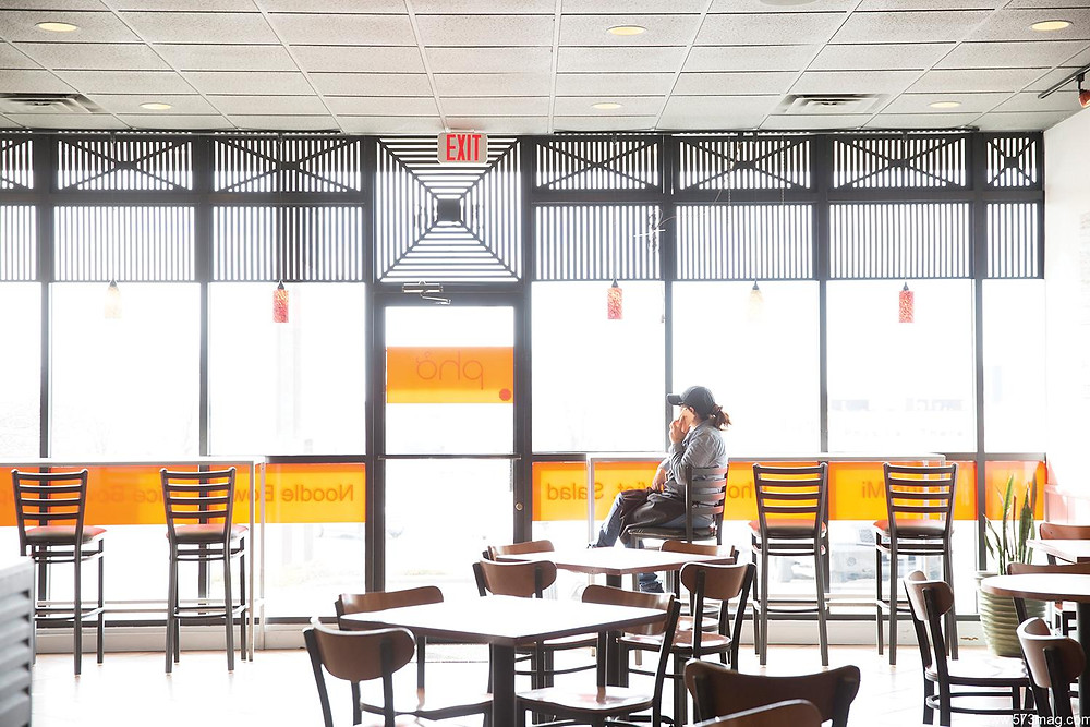 A woman sits in an empty restaurant about to open looking out the large front windows