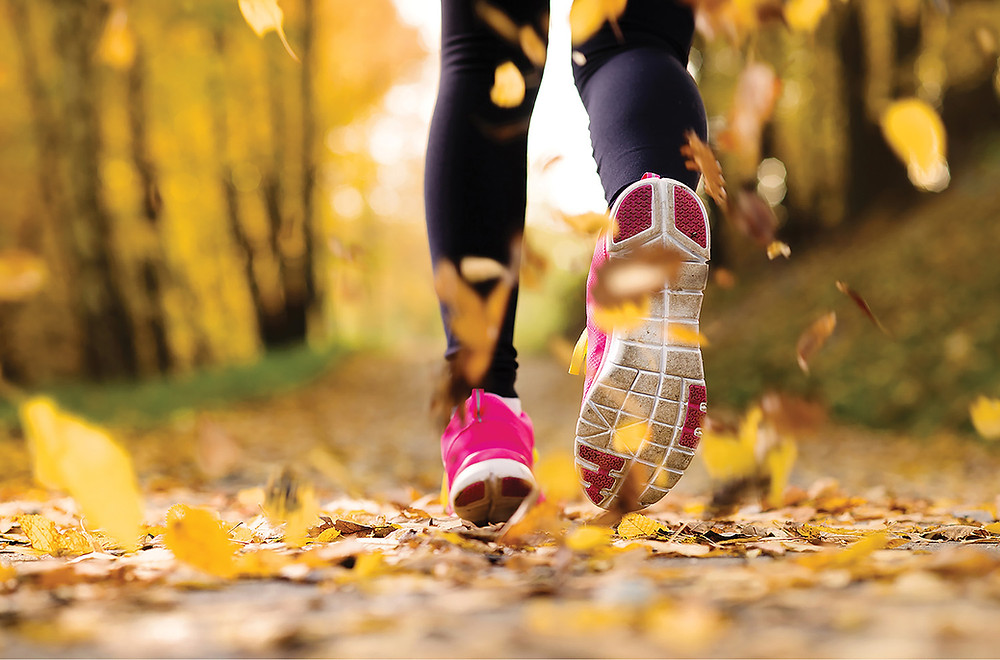 A woman's legs in athletic gear runs close to the lens on a leaf covered path through the woods in fall