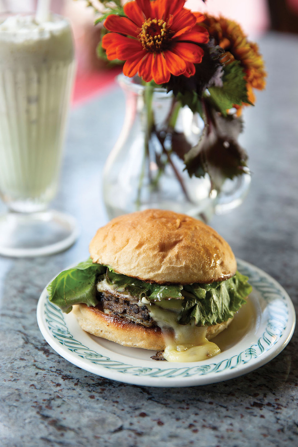 A burger with leafy greens, melty cheese, and a homemade bun on a plate with a mint shake and a vase of wild flowers setting behind it.