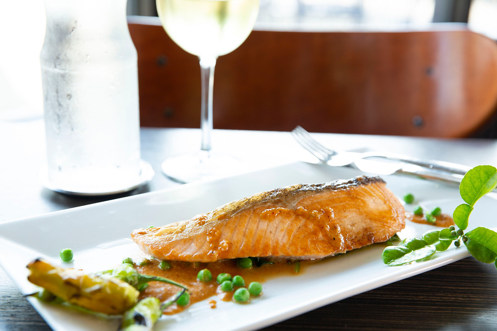 Grilled Salmon with an orange colored sauce, peas and a leafy garnish by a glass of white wine