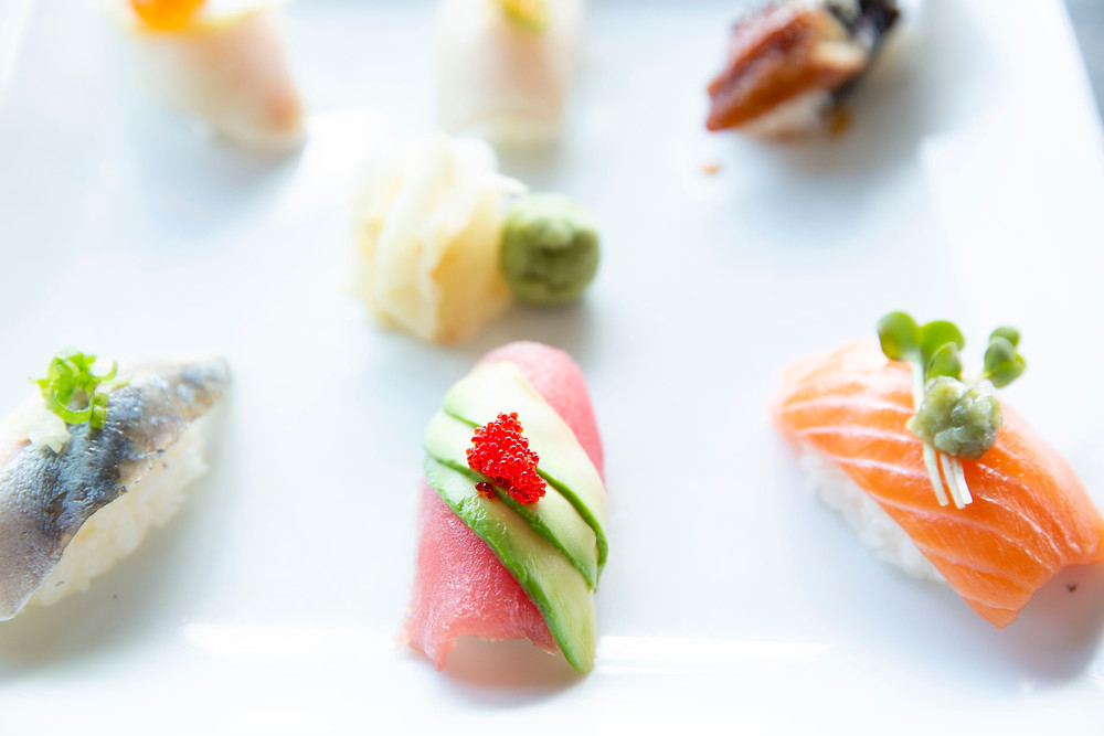 A sample plate of different sushi slices of all colors garnished and arranged beautifully and symmetrically.