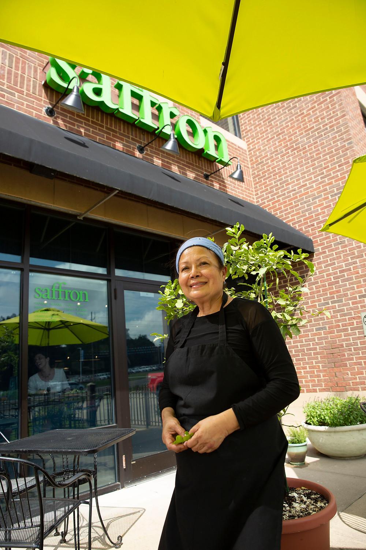 Vietnamese Chef, Su Hill smiles in her patio garden at Bistro Saffron