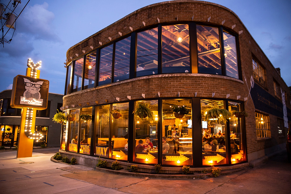 A 2 story building with wrap around windows covering the front and amber lights at dusk with a vintage sign lit up