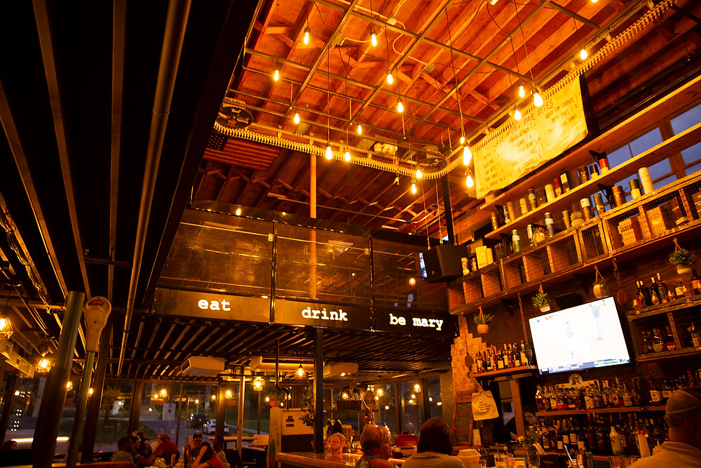 "Large bar with high ceilings and edison lights hanging low lighting up a huge selection of liquor and a sign ""Eat. Drink. Be Mary."""