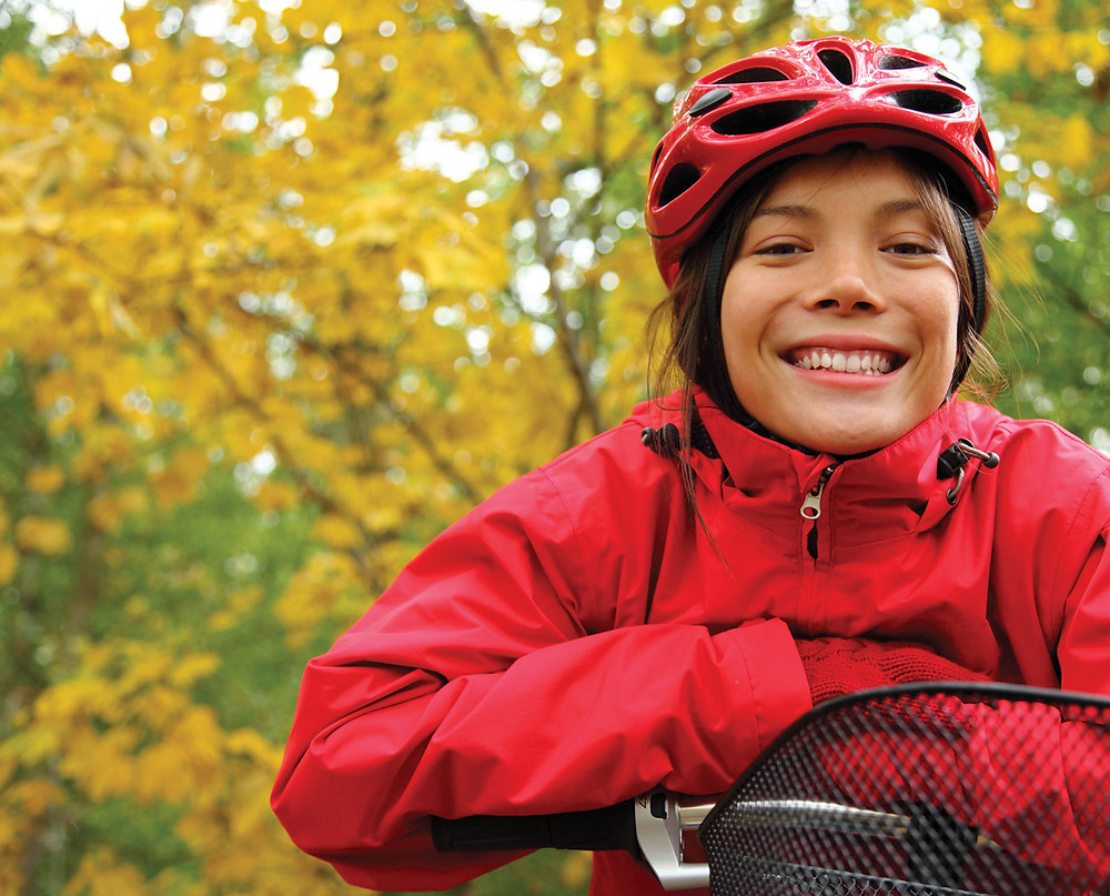 A young girl with her hair tucked into her coat and helmet leans on her bike's handle bars and grins big