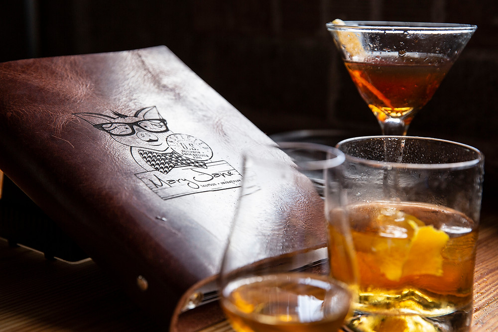 A leather drink menu with a cartoon pig wearing eyeglasses from Mary Jane Bourbon & Smokehouse by three cocktails in 3 different sized and shaped glasses