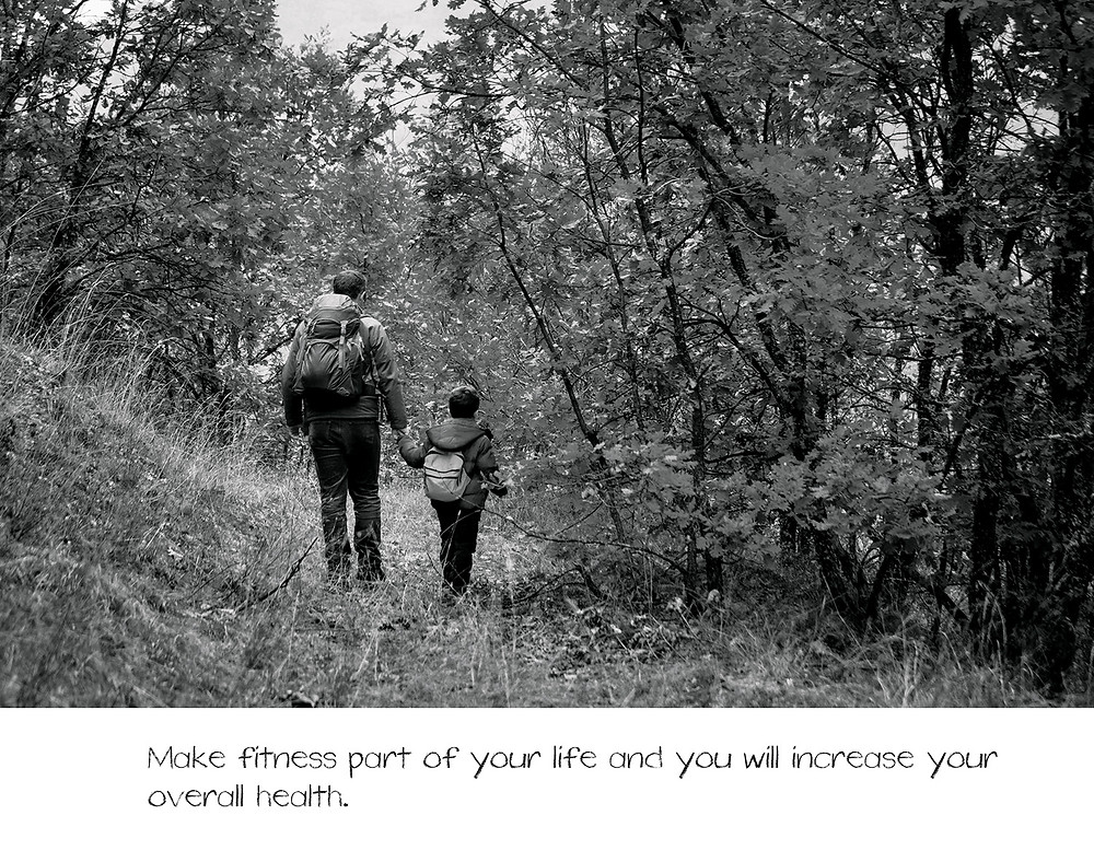 A little boy and his dad walk hand in hand through the woods with coats and napsacks