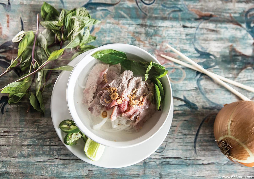 A dish of pork, noodles and parsley garnished with nuts, herbs, lemon and jalepeno.  sits on a wooden counter with chop sticks an onion and a sprig of mint