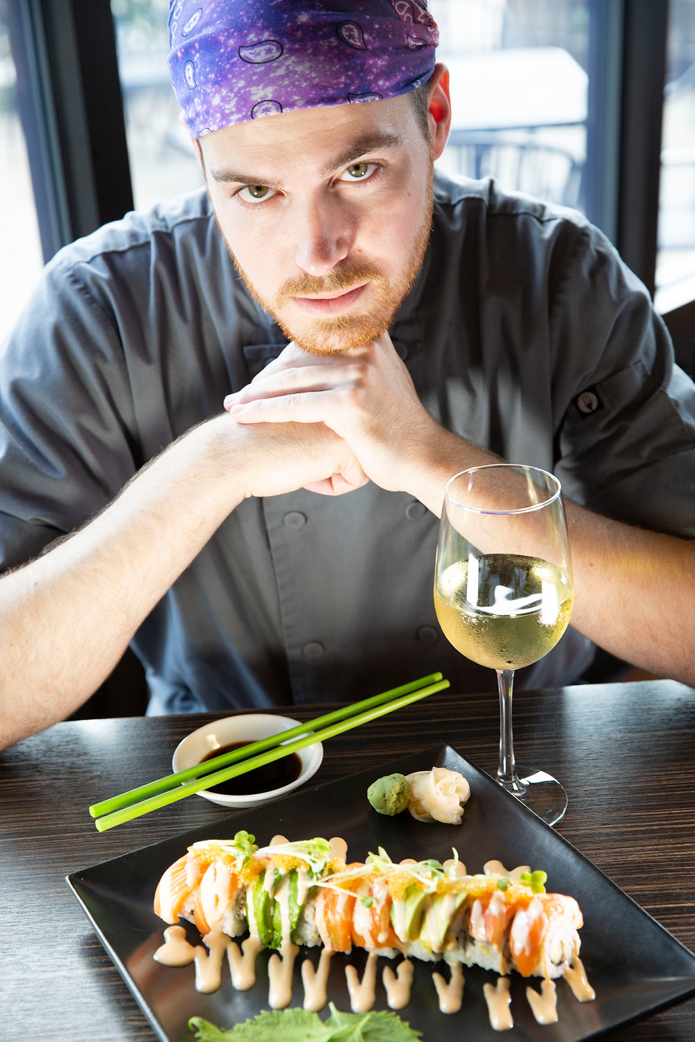 A young chef displays his handiwork, a sushi summertime roll with a spicy orange colored sauce zigzigged down the roll and a glass of white wine