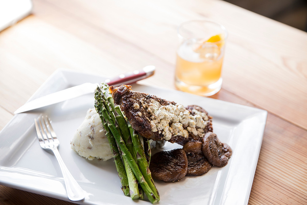 New York Strip + Red Mashed Potatoes, Grilled Mushrooms, Herbed Chèvre Cheese, and Asparagus  on a square plate by a gin and tonic with orange slice