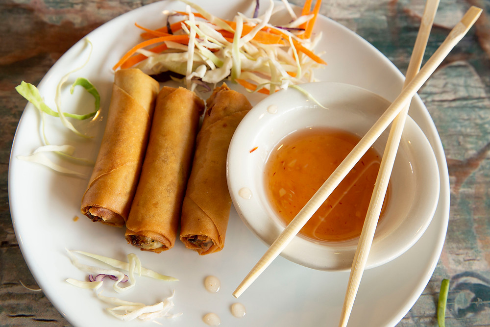 Three eggrolls sit on a plate with a small bowl of sauce, and fresh coleslaw salad. chopsticks lie across the bowl